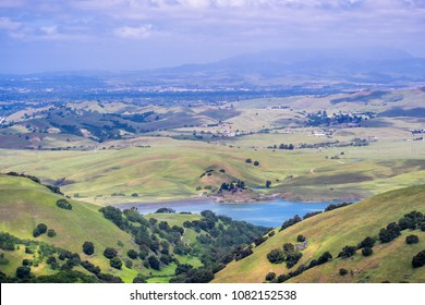 View towards San Antonio reservoir surrounded green hills; Pleasanton and Mt Diablo in the background, Alameda county, San Francisco bay area, California