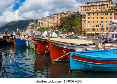 View of the town of Camogli on the Ligurian Riviera in Italy with its port. In the foreground, the typical colored fishing boats.