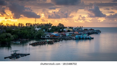 A view of the town of Sala Dan, Ko Lanta under a dramatic sunset sky with Ko Phi Phi in the background. Boats are moored close to the waterfront buildings.