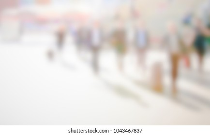 View of a trade show with people. Background with an intentional blur effect applied.