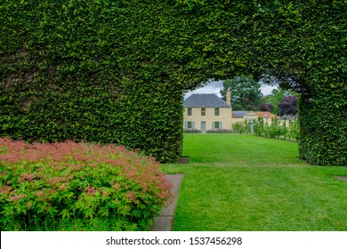 View of a traditional building through the opening in a long bush fence at the Royal Botanic Garden in Edinburgh, Scotland