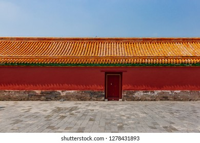 View of traditional Chinese red wall and yellow roof tiles with closed door, in Forbidden City, in Beijing, China
