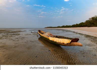 View of a traditional fishing canoe at the beach in the island of Orango at sunset, in Guinea Bissau. Orango is part of the Bijagos Archipelago; Concept for travel in Africa and summer vacations