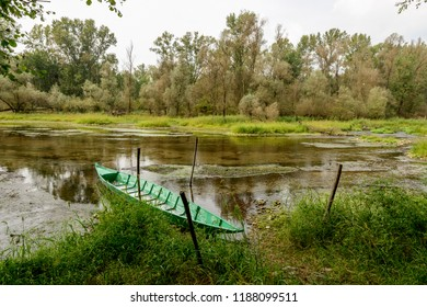 view of traditional green metal boat moored in oxbow lake at Ticino river , shot in a bright cloudy fall day  in Ticino park near Bernate, Milan, Lombardy, Italy