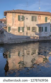 view of traditional house and its reflection in waters of artificial historic canal, shot in winter bright light at Bernate Ticino, Milan, Lombardy, Italy