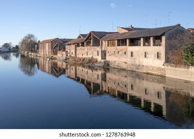 view of traditional houses on embankment of artificial historic canal, shot in winter bright light at Bernate Ticino, Milan, Lombardy, Italy