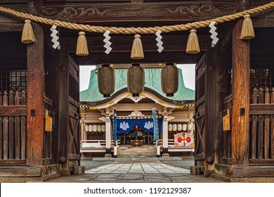 View of Traditional Japanese Temple through Large Wooden Gate Building with Hanging Shimenawa Rope and Decorative White Paper Lanterns (Okayama, Japan).