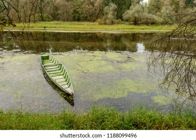 view of traditional metal boat moored in oxbow lake at Ticino river , shot in a bright cloudy fall day  in Ticino park near Bernate, Milan, Lombardy, Italy