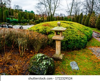 View of a traditional stone lantern ishi-doro or ikekomi-doro surrounded by decorative boulders and bushes in a Japanese garden in Bonn, Germany .