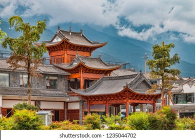 View of Traditional Temple Building in Historic Neighborhood of Chinese City. Beautiful Bai Temple with View of Cloud Covered Mountains in Distance (Dali, Bai Autonomous Prefecture, Yunnan, China).