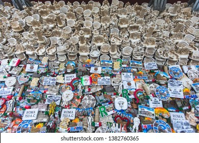 """View of traditional tourist souvenirs and gifts from Rome and Vatican, Italy, with fridge magnets with text """"Rome"""", miniature toys in local vendor souvenir shop of Trevi Rioni"""