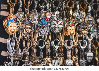"""View of traditional tourist souvenirs and gifts from Venice, Italy and with toys, masquerade venetian masks, fridge magnets with text """"Venice"""" and key ring keychain, in local vendor souvenir shop"""