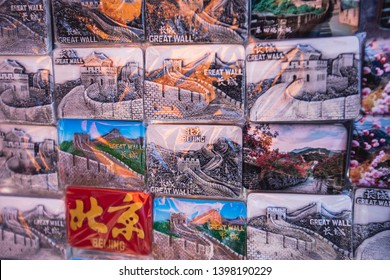 """View of traditional tourist souvenirs and gifts from Beijing, China, with fridge magnets with text """"China"""", and """"Great Wall"""" miniature toys in local vendor souvenir shop in Panjiayuan Market"""