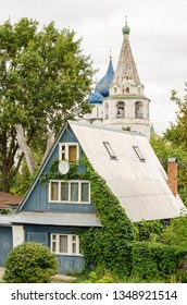 View of a traditional wooden house and the Suzdal Kremlin in the background