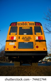 A view of a traditional yellow school bus from the rear.