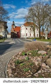 """Aussicht von einer Verkehrsinsel mit Frühlingsblumen auf die Kapelle """"Heilig-Geist"""" in Angermuende"""