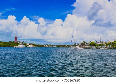 View of tranquil harbour with sailboats, Elbow Reef Lighthouse, blue sky and white clouds in the background. Hope Town, Marsh Harbour, Abaco, The Bahamas.
