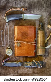 Up view travel adventure kit maked from vintage stuff: knife, leather notebook, spyglass, pocket watch, pocket knife, leather skull sheath. HDR