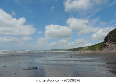 A view from Tregantle beach and Whitsand Bay in Cornwall, looking west towards Looe, with blue sky and clouds reflected in the sea