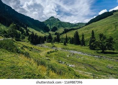 View of a Tristkogel, a sharp high alpine peak in the summer mountain landscape. Blue sky, clowds, green meadows and trees, flowing creek. Saalbach Hinterglemm valley, High Tauren, Austria.