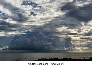 View from a tropical beach to a threatening big dark cloud formation, from which rain falls - Location: Seychelles