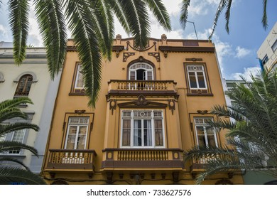 a view trough palms of an orange old house in las palmas downtown on gran canaria island.