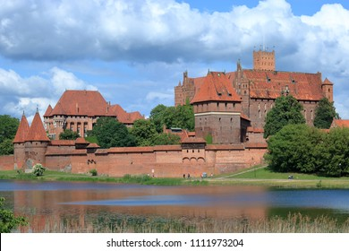 View at tuetonic castle in Malbork, Poland, from opposite river bank, next to building green trees and bushes, blue sky with picturesque swirling clouds