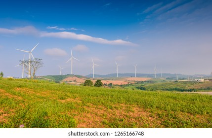 View of turbine on mountain. Windmill turbine for electric production with blue sky and Growing agricultural plots at Khao Kho, Petchaboon, Thailand. Power and energy concepts