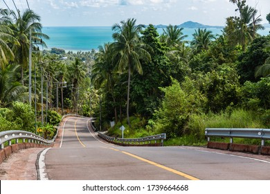 View of turquoise colored sea from altitude on the resort island. Deserted winding asphalt road descending to the coast and passing through the tropical palm jungle. On the horizon, see another island
