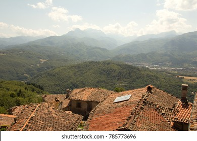 View of Tuscan rooftops and mountains from above.