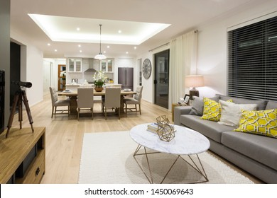 A view of TV room decorated with contemporary center table, wooden TV counter, cushioned sofa and a 6-seater dining table attached to modular kitchen.