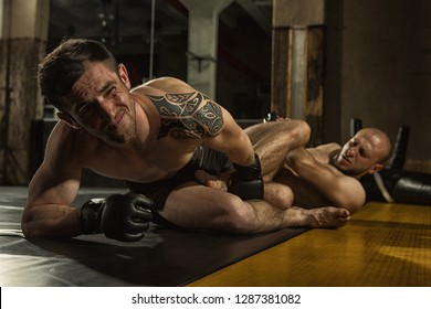 View of two aggressive sportsmen wearing gloves and shorts grappling on training in gym. Muscular tattooed MMA fighter with angry expression looking away and keeping with leg his opponent who lying.