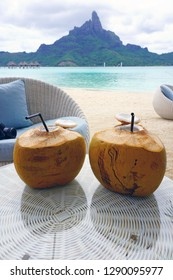 View of two fresh drinking coconuts on a table in front of the Mont Otemanu mountain in Bora Bora, French Polynesia, South Pacific