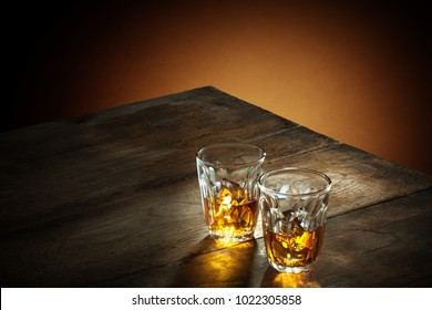 view of two glasses of  whiskey on color background.