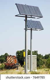 A view of two large solar panels used to power signals and safety equipment associated with a railroad crossing.