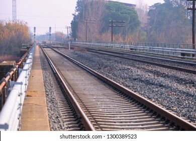 View of two parallel tracks on the railway near a station