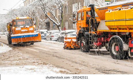 view of two snow plough vehicles in one winter day in Europe during heavy storm