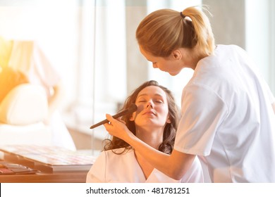 View of Two young beautician students working during make up classes