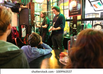 View of two young men playing guitar and singing in a pub in Dublin Irlande called Bad ass temple bar. The standing musicians are in front colorful high windows. Picture taken on 14th august 2016.