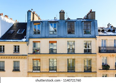 View to typical facade of parisian building. Traditional french old house with typical balconies, windows, rooftops and chimney pots. Cityscape from window. Paris, France. Architecture at city street.