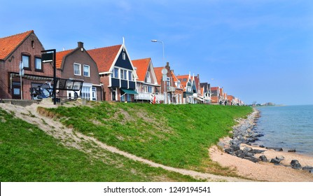 View of the typical fishing houses in Volendam and Markermere Bay. Blue sky, green grass. Volendam, Netherlands.