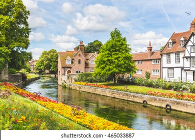 View of typical houses and buildings in Canterbury, England. Flowers and trees along the canal in summer. Postcard image on a sunny day. Architecture, nature and travel concepts.