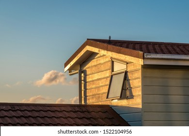 View of typical New Zealand suburban house with weatherboard cladding wall, concrete tile roof and awning window