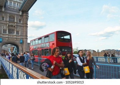 View to a typical red London bus and pedestrians on the walkway of the Tower Bridge - London, Great Britain - 08/01/2015