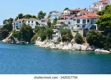 View of typical white houses of Skiathos town in Skiathos island, Aegean sea, Greece. Skiathos town on Skiathos Island, Greece. Beautiful view of the old town with boats in the harbor.