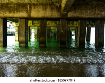View under the concrete pier with turquoise sea at seaside of tropical island in summer. Scene beneath the bridge with a lot of concrete pillar, wave on the beach and sea water and leading lines.