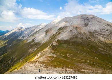View from under the peak Vihren to the marble part of Pirin mountain, Bulgaria. Hiker in distance alone on long curvy highland trail over steep mountain range.