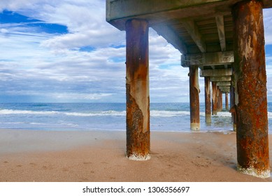View under a pier stretching out to the ocean in St. Augustine Beach, Florida, USA (St. Johns County Pier)