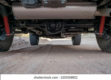 View of the undercarriage (underside) of an off road 4x4 vehicle out on a dirt trail in the desert
