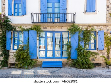 View of unidentified village house with blue windows and doors at Alacati charming Streets , a popular destination for traveling and vacation in Izmir,Turkey.